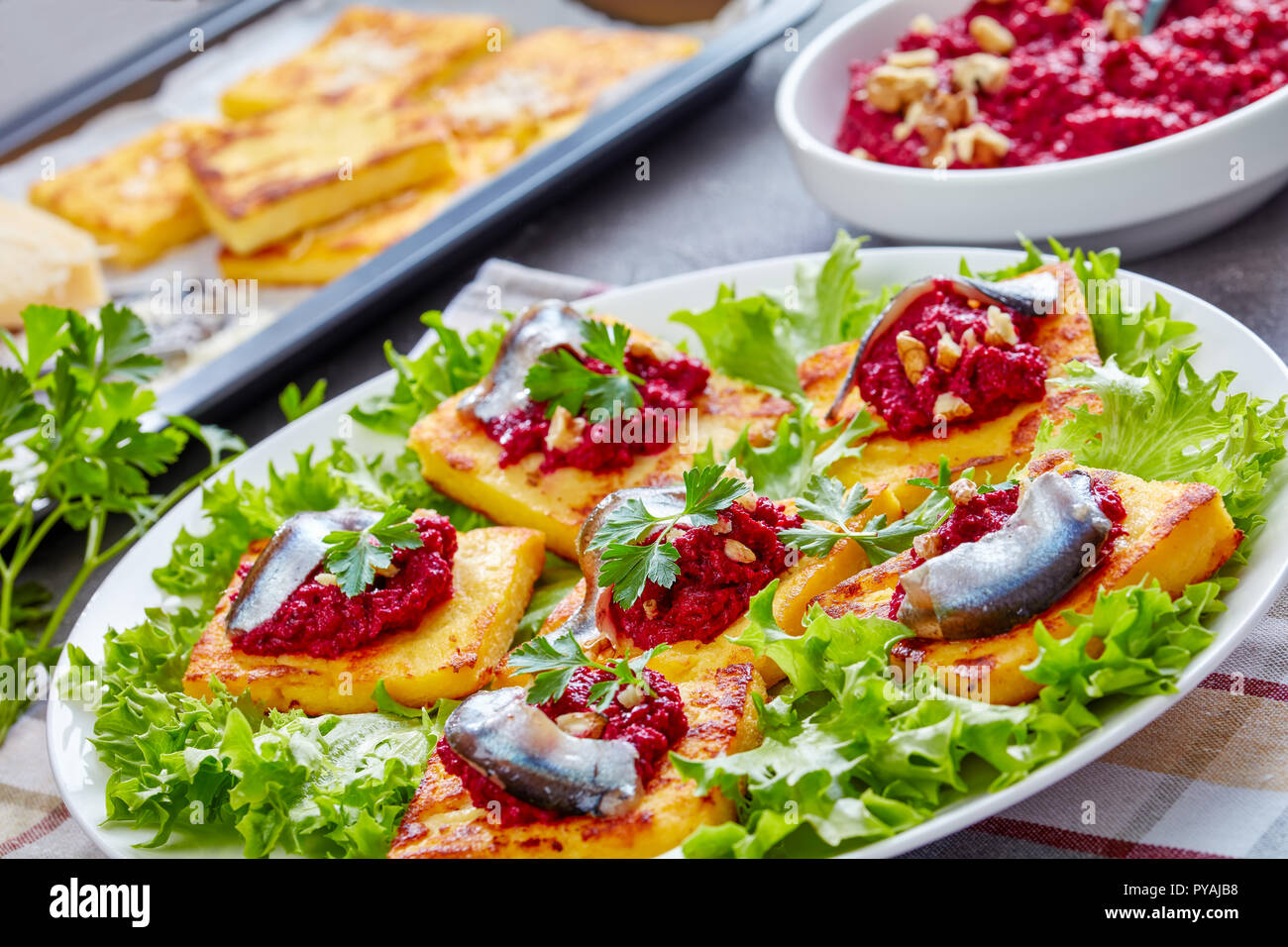 close-up of Polenta Squares with Creamy beetroot puree, topped with anchovies and parsley on a white plate. freshly baked polenta bars and parmesan on - Stock Image