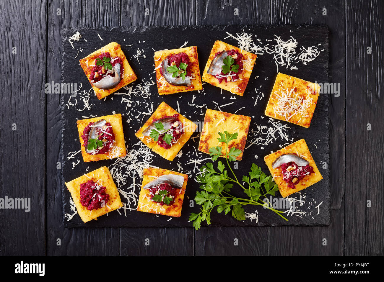 overhead view of portions of Polenta Squares with Creamy beetroot pate, topped with anchovies and parsley served on a black stone tray on a wooden tab - Stock Image