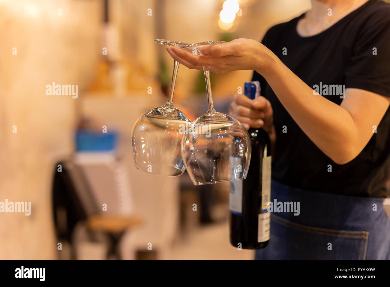 Glass of wing in waitress is hand with bottle red wine in background. Stock Photo