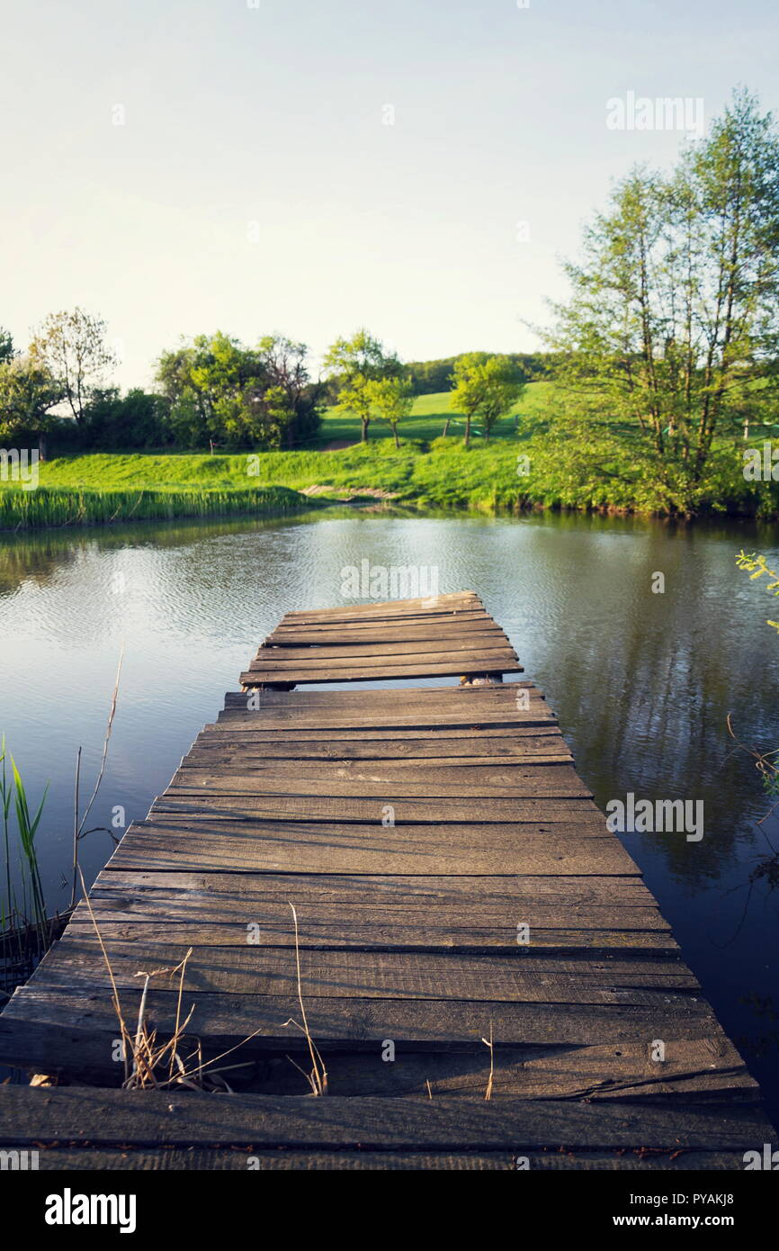 Pretty wooden pier at pond during sunset, colorful summer day, new life change concept, fresh start, new year resolution, dieting and healthy lifestyl - Stock Image