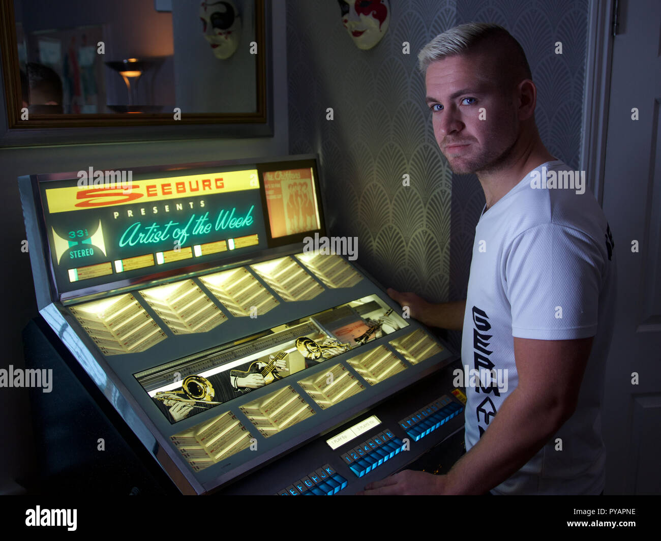 A young man standing by a Seeburg juke box, looking at camera ,  England Stock Photo