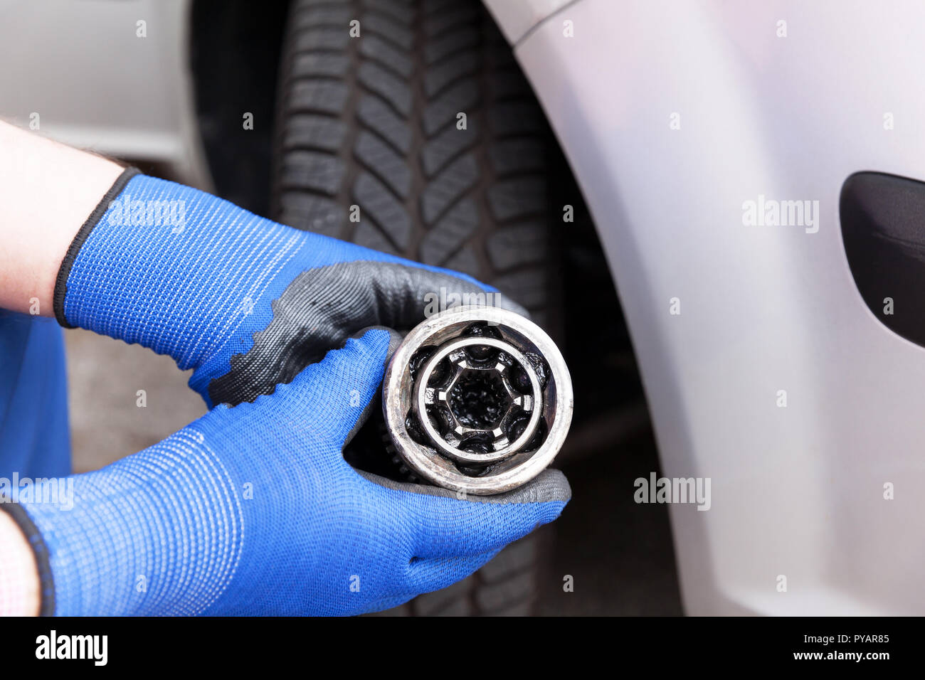 Automechanic, wearing blue work gloves, holding an old constant velocity joint in front of the car. Car service, vehicle parts replacement - Stock Image