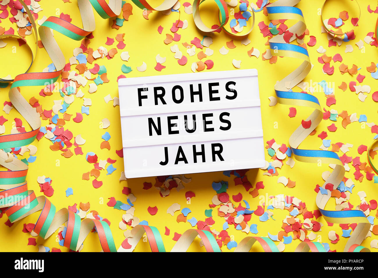 Frohes neues Jahr means happy new year in German - party celebration flat lay with confetti and streamers on yellow background - Stock Image