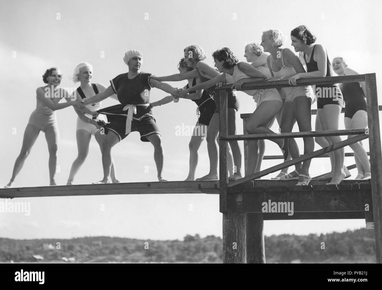 Having fun in the 1930s. Actor Nils Ericson in a bit of a situation when being torn from both sides. The women are wearing bathing suits and he looks as if he does to in an odd design. At a filmset from unknown swedish film from the 1930s. - Stock Image