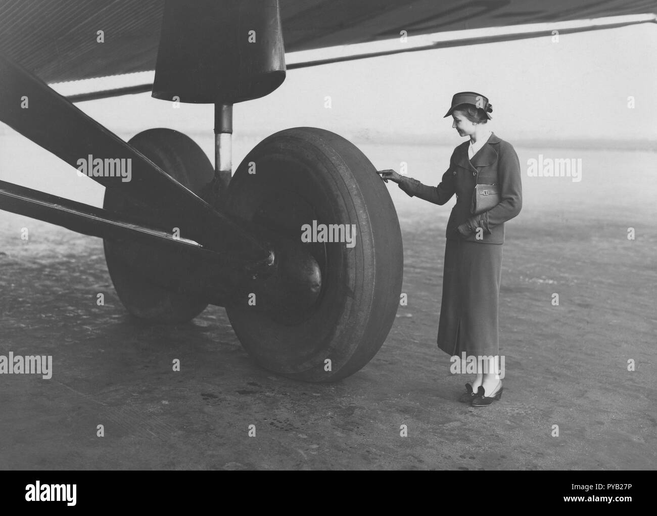 Airplane in the 1930s. A well dressed young woman looks small when comparing her size to the giant wheels on the landing gear to this german Junker G38 aircraft. It was used between Berlin and London from July 1 1931 and was at that time the largest four engined passenger aircraft, with 34 passengers and seven crew members. - Stock Image