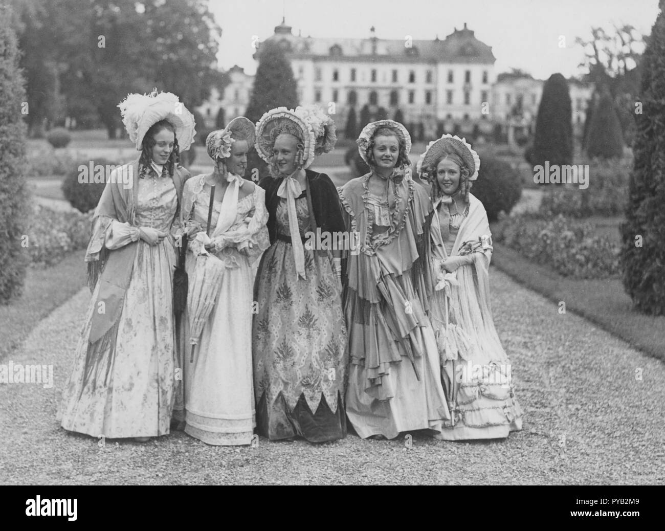 Poke bonnets. A group of five young women in the park of Drottning holm castle,  during the filming of the movie Filmen om Emelie Högqvist 1939. They are all dressed up as ladies of the year 1835. Especially the hats whitch are called Poke bonnet that came into fashion at the beginning of the 19th century. - Stock Image