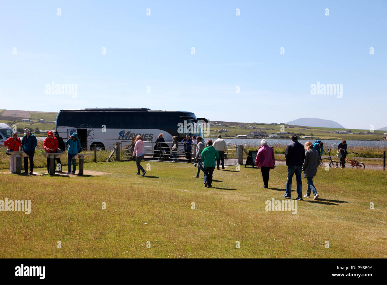 Visitors returning to their coach after a visit to the Standing Stones of Stenness, a Neolithic monument on Orkney, Scotland - Stock Image