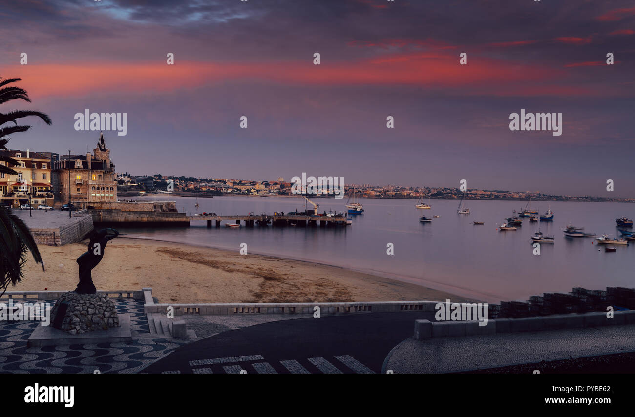 Empty sandy Praia do Ribeiro and fishing boats an bay with magenta sunset in Cascais, Portugal - Stock Image