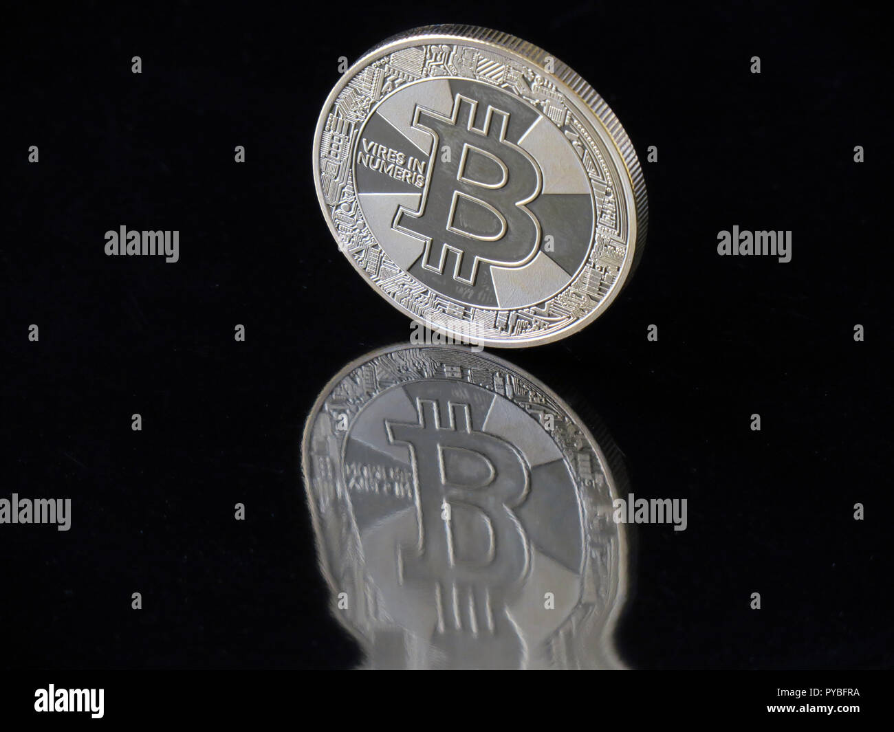 """Berlin, Germany. 30th Aug, 2018. 30 August 2018, Germany, Berlin: A Bitcoin coin with the imprint """"Vires in Numeris"""" (strength in numbers) reflects distorted in a black area. The digital currency has been around for ten years now and is based on blockchains (chains of data blocks) in which Bitcoin units are generated in mathematical operations on the computer. Credit: Soeren Stache/dpa-Zentralbild/ZB/dpa/Alamy Live News Stock Photo"""