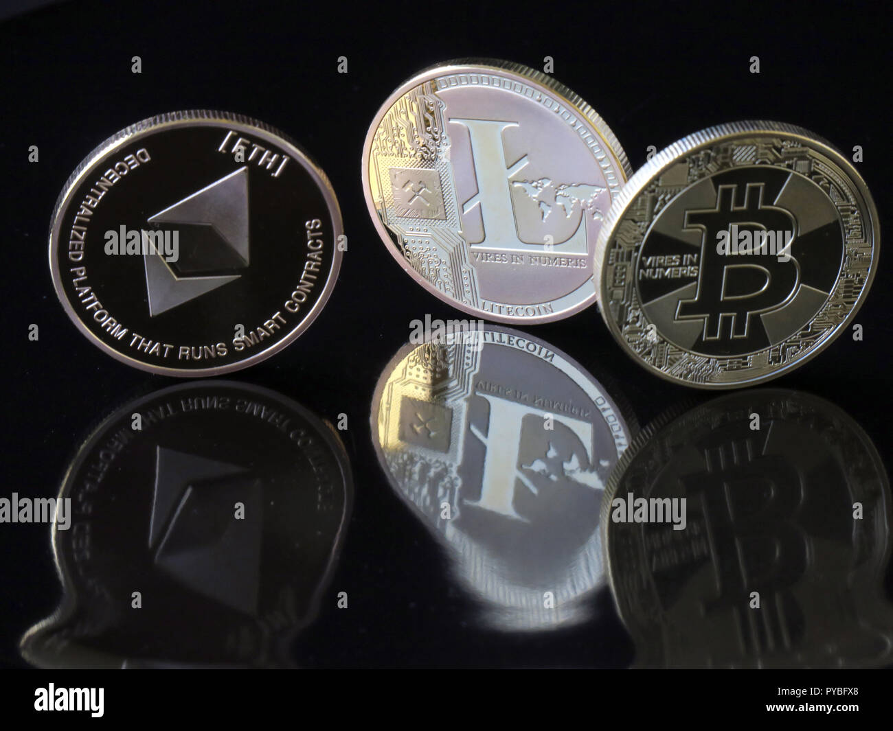 """30 August 2018, Berlin: 30 August 2018, Germany, Berlin: A (L-R) Etherum Classic coin with the imprint """"ETH"""", a Lite coin and a Bitcoin coin with the imprint """"Vires in Numeris"""" (strength in numbers) are reflected distorted in a black surface. The digital currency Bitcoin has been around for ten years now and is based on blockchains (chains of data blocks), in which Bitcoin units are generated in mathematical operations on the computer. After Bitcoin, the Internet currency Etherum is the world's second largest virtual payment method. Photo: Soeren Stache/dpa-Zentralbild/ZB Stock Photo"""