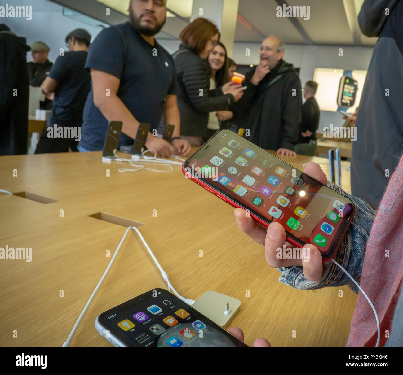 Customers in the Apple store in the Meatpacking District in New York try out the new relatively affordable iPhone XR on Friday, October 26, 2018, the first day they went on sale.  The new phones, anxiously awaited by drooling iPhone aficionados, sell for a base $749 as opposed to the previously released XS and XS Max which sell for a whopping $999 and $1099. In addition the XR comes in an array of colors. (© Richard B. Levine) - Stock Image
