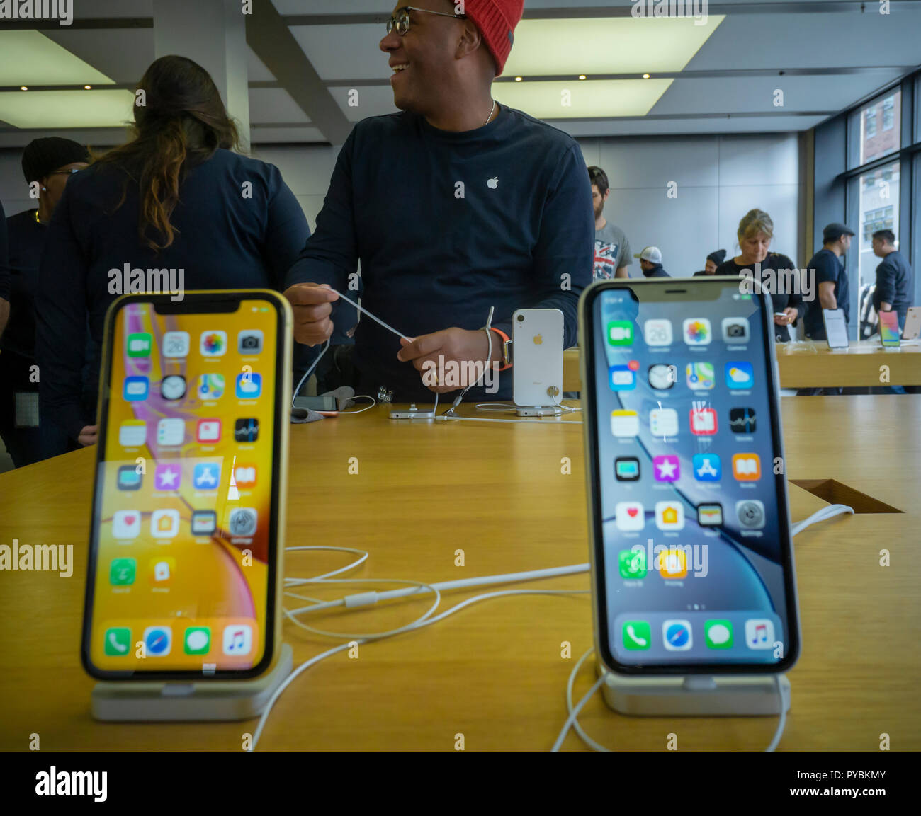 An Apple employee in the Apple store in the Meatpacking District in New York adjusts the security cables of the display of the new relatively affordable iPhone XR on Friday, October 26, 2018, the first day they went on sale.  The new phones, anxiously awaited by drooling iPhone aficionados, sell for a base $749 as opposed to the previously released XS and XS Max which sell for a whopping $999 and $1099. In addition the XR comes in an array of colors. (© Richard B. Levine) - Stock Image