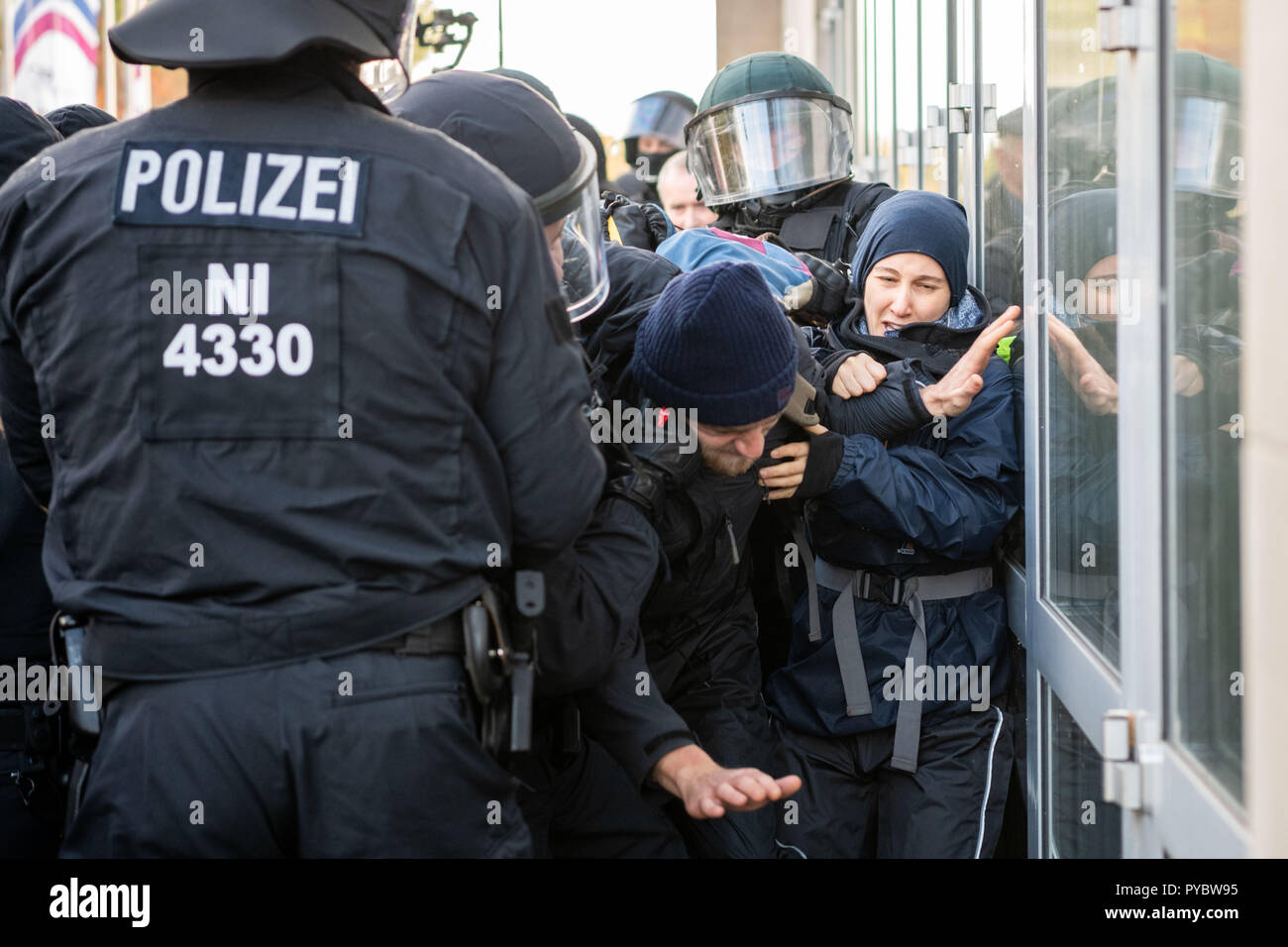 Oldenburg, Germany. 27th Oct, 2018. Policemen preventing demonstrators from blocking the way of AfD members to the state party conference of AfD Lower Saxony in Oldenburg's Weser-Ems-Halle. Credit: Mohssen Assanimoghaddam/dpa/Alamy Live News - Stock Image