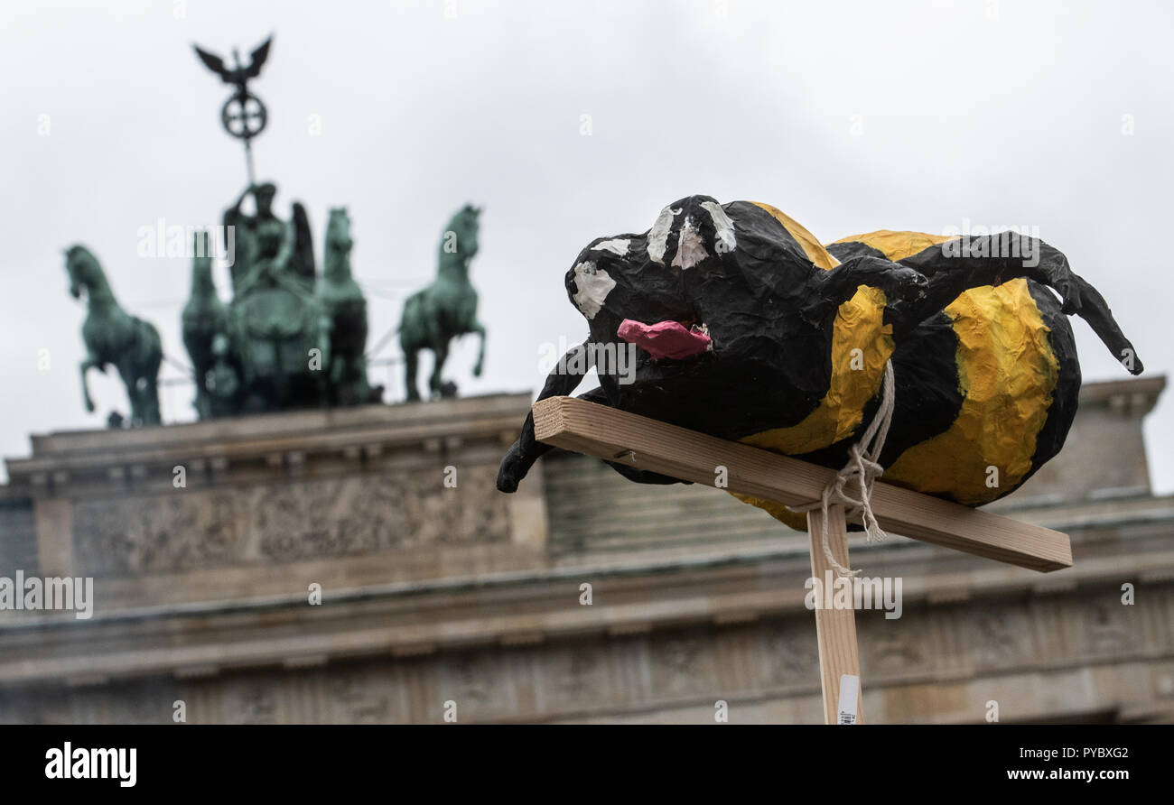 Berlin, Germany. 27th Oct, 2018. A demonstrator holding up on a stick an oversized papier-mâché bee at a protest rally for sustainable agricultural subsidies of the 'we're fed up' alliance at the Brandenburg Gate with the slogan 'Make steam for bee-friendly agriculture'. Credit: Paul Zinken/dpa/Alamy Live News - Stock Image