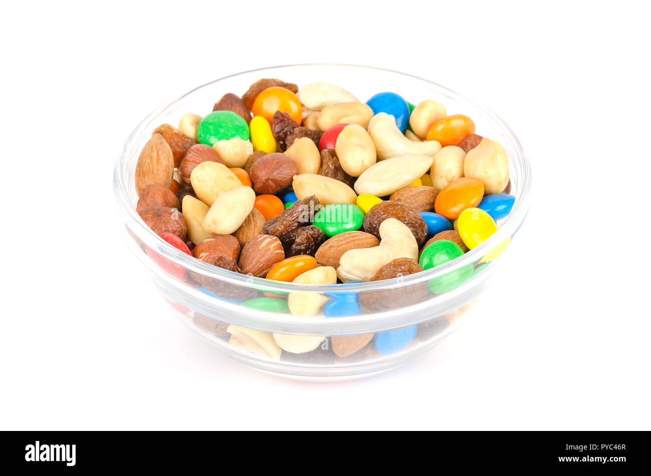 Trail mix in glass bowl. Snack mix. Almonds, cashews, peanuts, hazelnuts, raisins and colorful chocolate candies. Food to be taken along hikes. - Stock Image