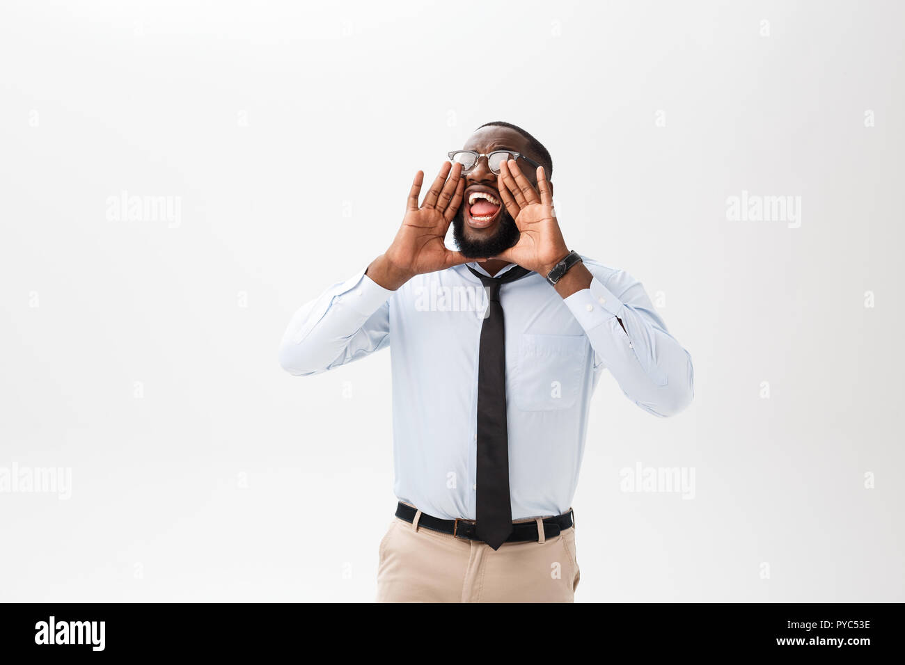 African man yelling with hand on his mouth isolated on a white background. - Stock Image
