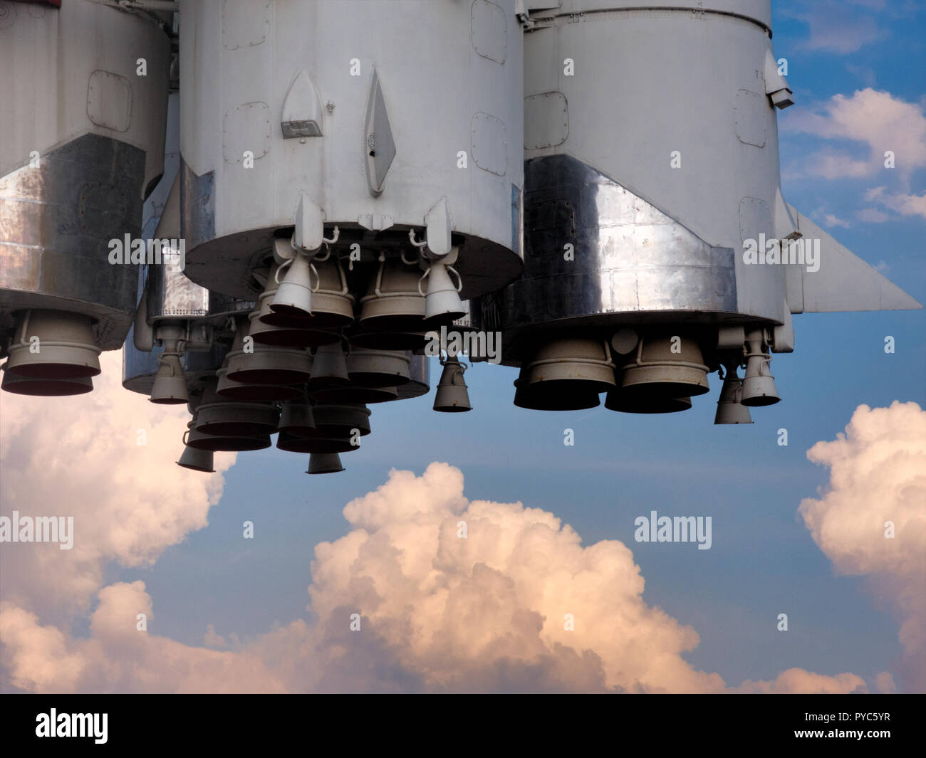 Bottom part of the space rocket, cloudy summer sky at background - Stock Image