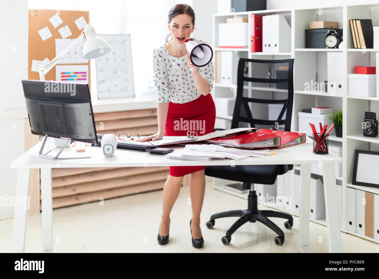 A young girl stands in the office near the table and says in a shout. - Stock Image