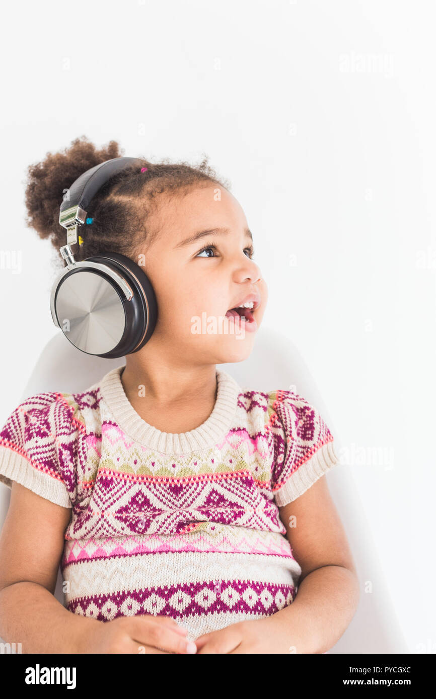 Cute Little Girl In A Colorful Dress Listening To Music With