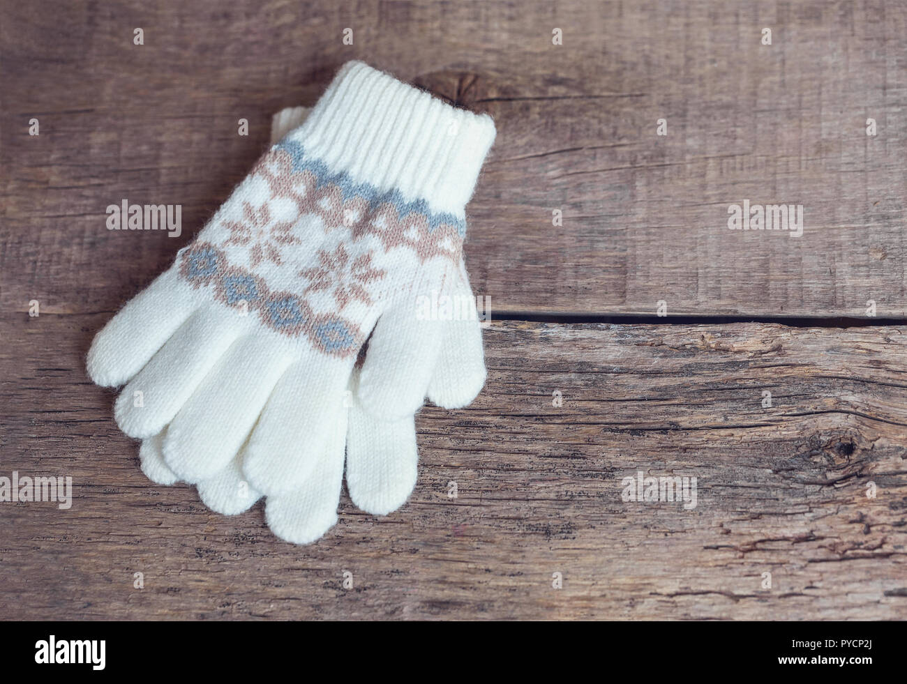 Winter children's mittens lie on a wooden background. Hygge - Stock Image