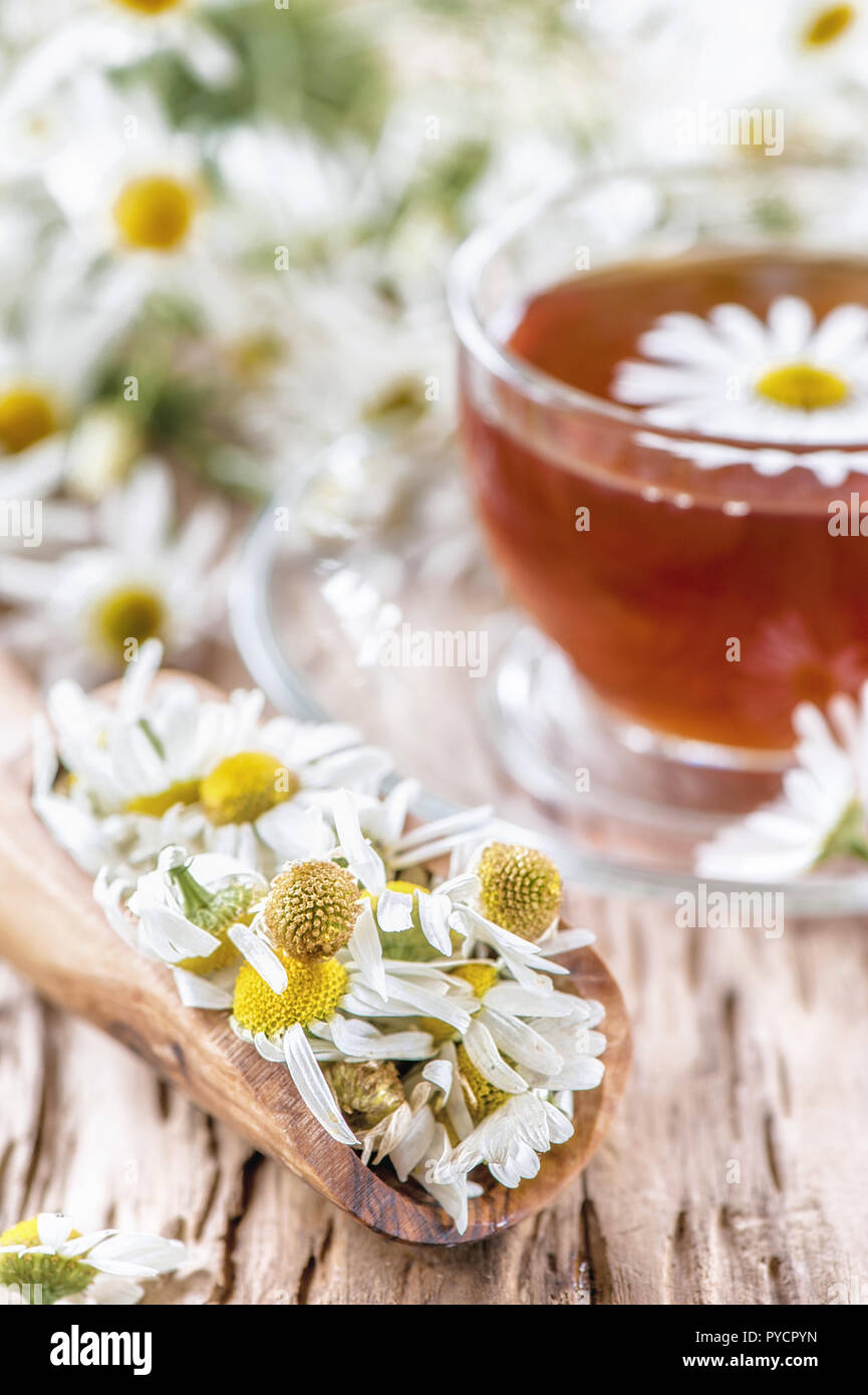 A clear Cup of medicinal chamomile tea on an old wooden table. Health and healthy lifestyle concept. - Stock Image