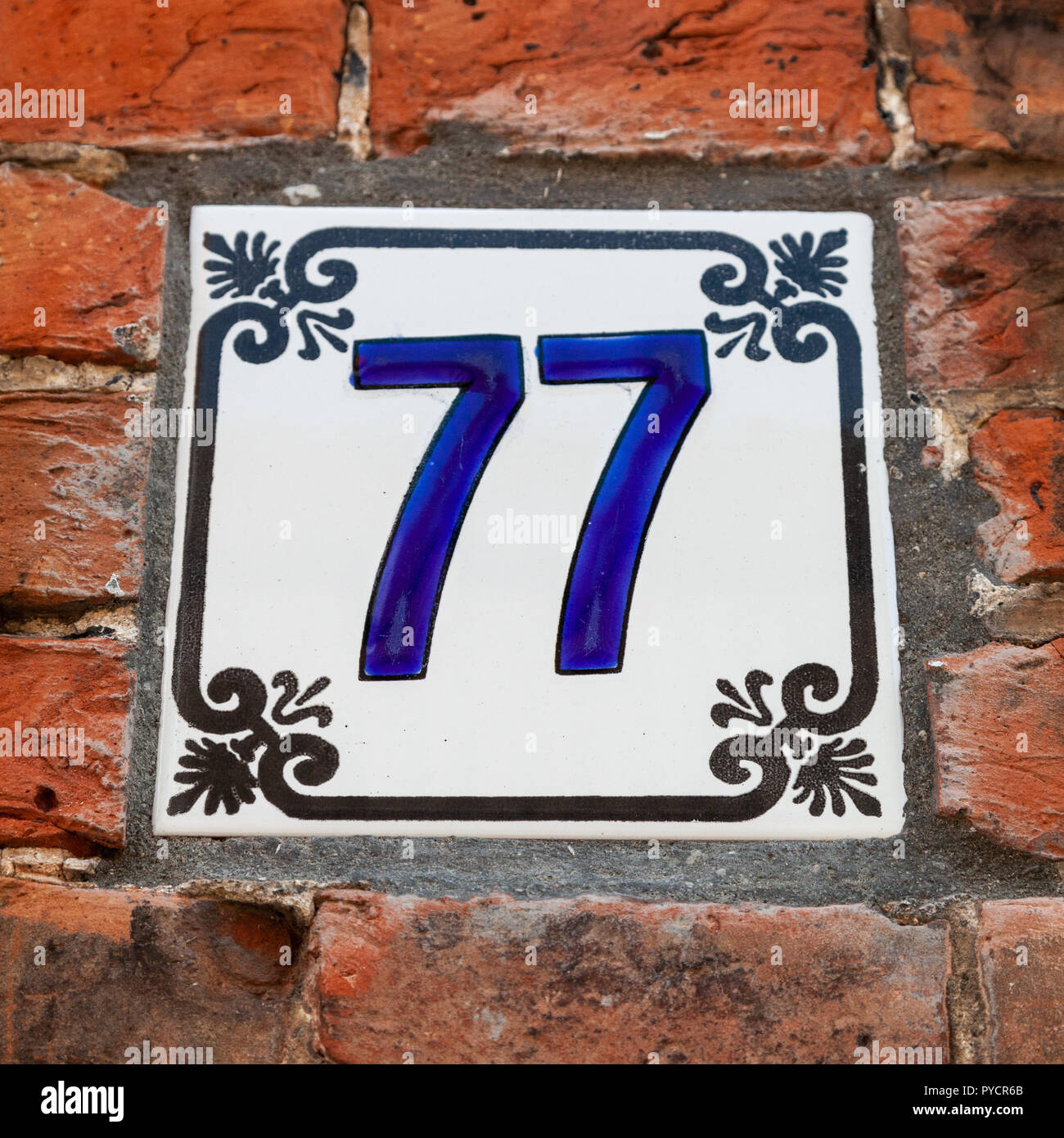House number seventy-seven 77 painted on ceramic tile in blue and black  with fleur-de-lis pattern from Sweden or Belgium - Stock Image