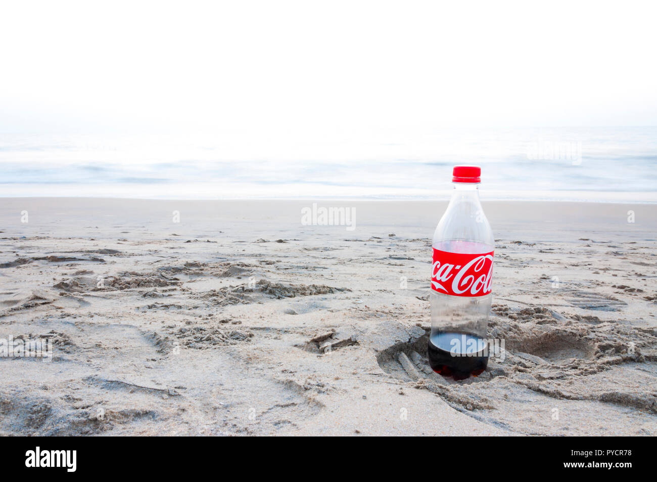 Kochi, Kerala, India - January 11, 2015: Almost empty plastic Coca Cola bottle left on a footprint in the sand on Arabian sea beach in Kochi. - Stock Image