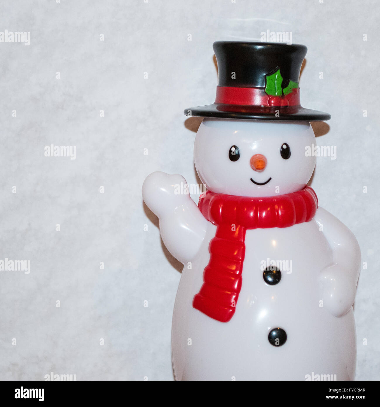 Toy snowman waving with white scarf and black top hat with red sash. There is a white background. Stock Photo