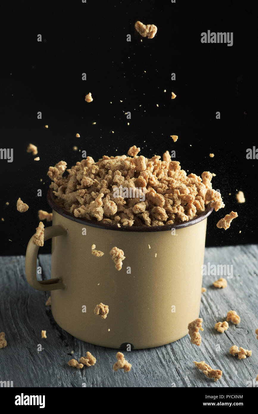 some chunks of textured soy protein in an old beige enamelware pot, placed on a rustic gray wooden table, against a black background - Stock Image