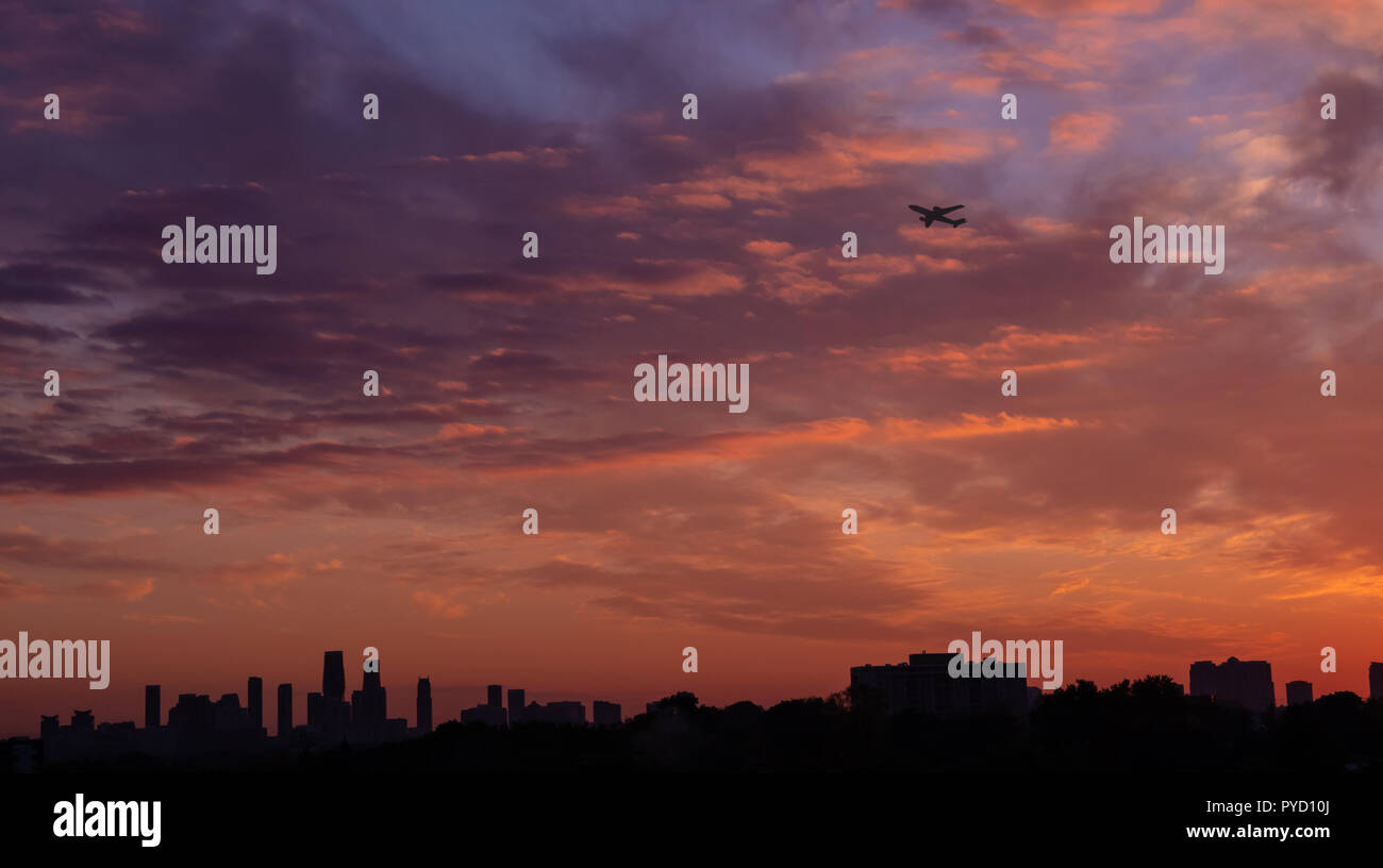 Dramatic sunset skyline in Mississauga, Ontario with buildings silhouettes and airplane taking off - Stock Image