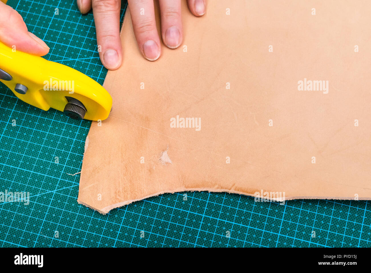 workshop of making the carved leather bag - craftsman cuts edge of rough vegetable tanned leather by rotary cutter - Stock Image