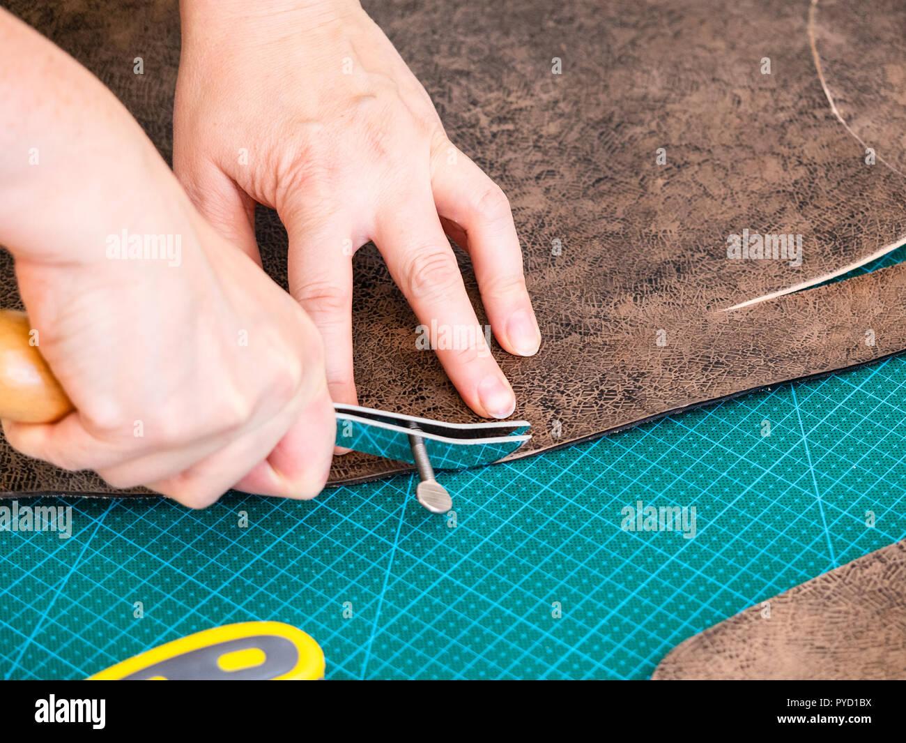 workshop of making the carved leather bag - craftsman marks pattern on the carved leather for handbag by adjustable edge creaser tool - Stock Image