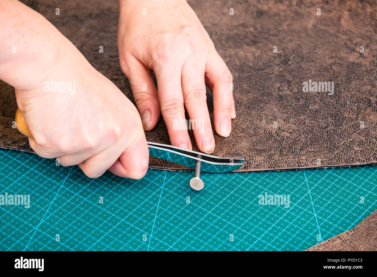 workshop of making the carved leather bag - craftsman draws pattern on the carved and colored leather for handbag by adjustable edge creaser tool - Stock Image