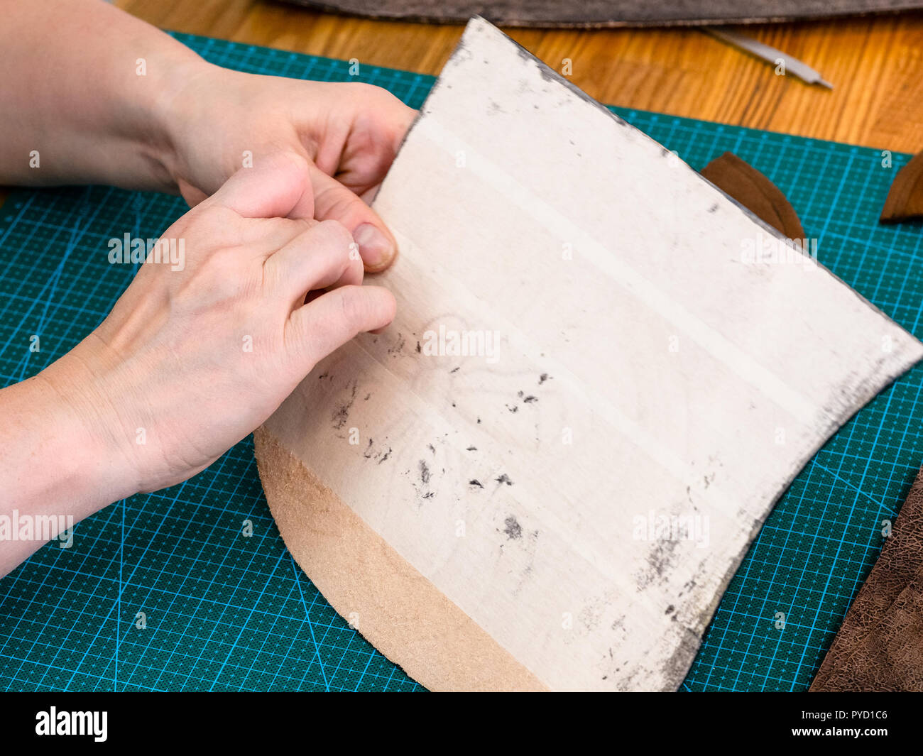 workshop of making the carved leather bag - craftsman removes the protective fabric from the back side of leather item of the handbag - Stock Image