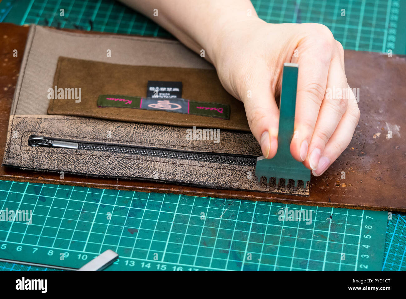 workshop of making the carved leather bag - craftsman punches leather edge of inner pocket for handbag by stitching punch - Stock Image