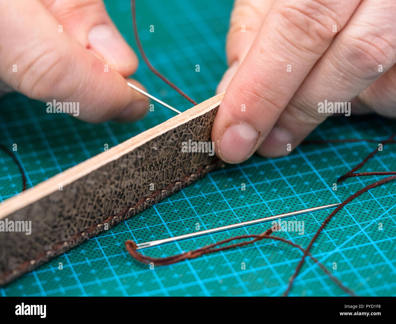 workshop of making the carved leather bag - craftsman stitches the carved brown belt for leather handbag by needle with thread - Stock Image