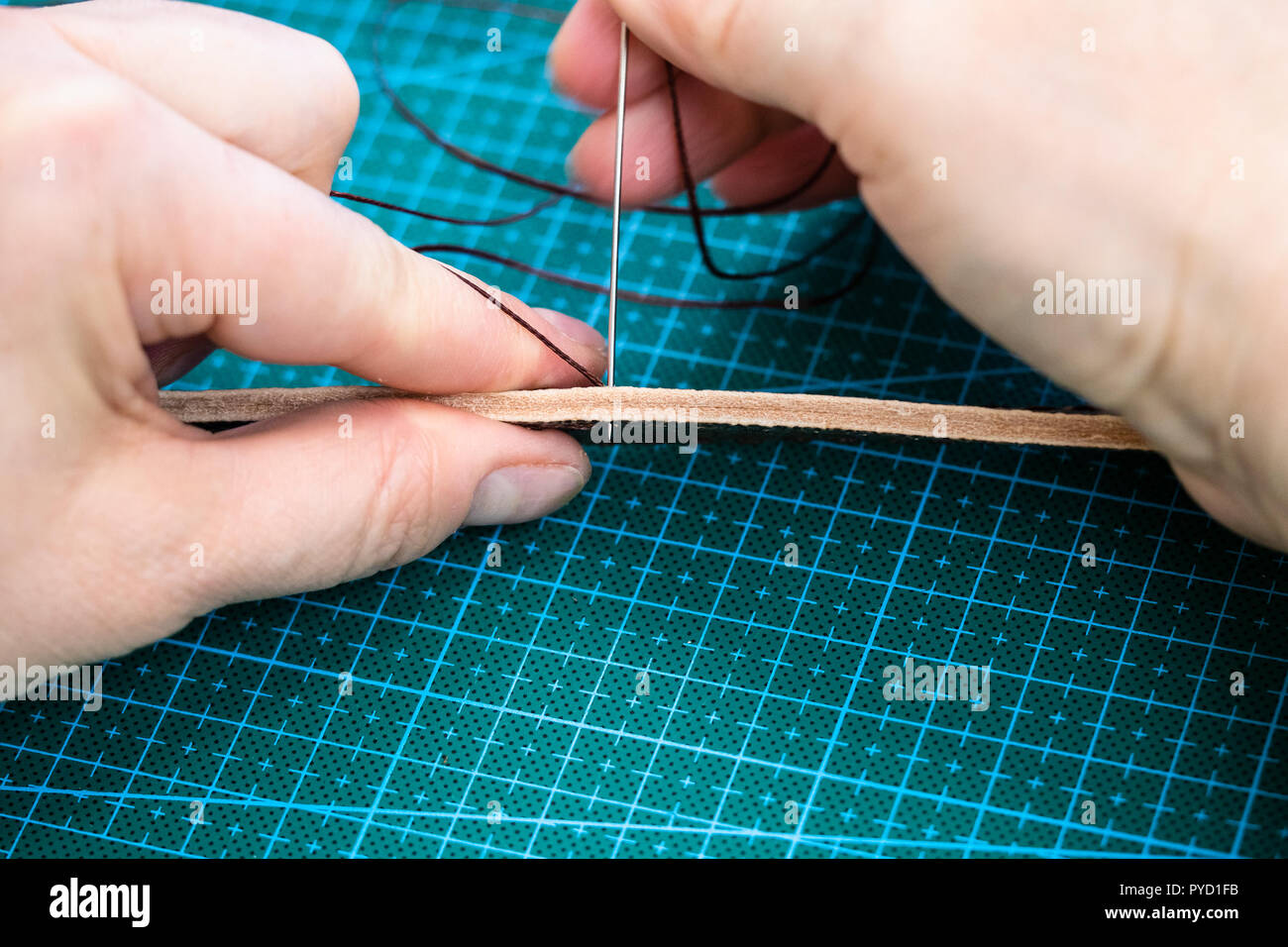 workshop of making the carved leather bag - craftsman sews the belt for leather handbag by needle with thread - Stock Image