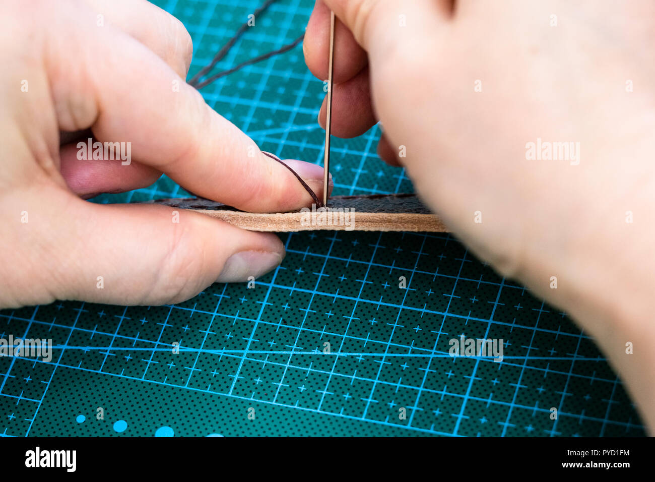 workshop of making the carved leather bag - craftsman stitches the belt for leather handbag by needle with thread - Stock Image