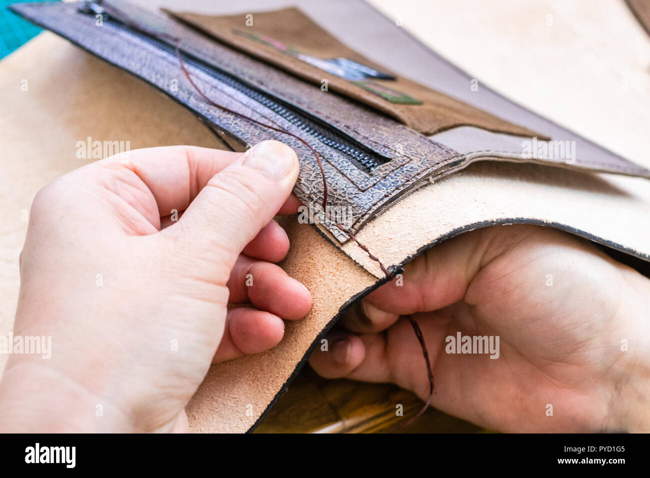 workshop of making the carved leather bag - craftsman stitches the inner pocket in leather handbag by needle with thread - Stock Image