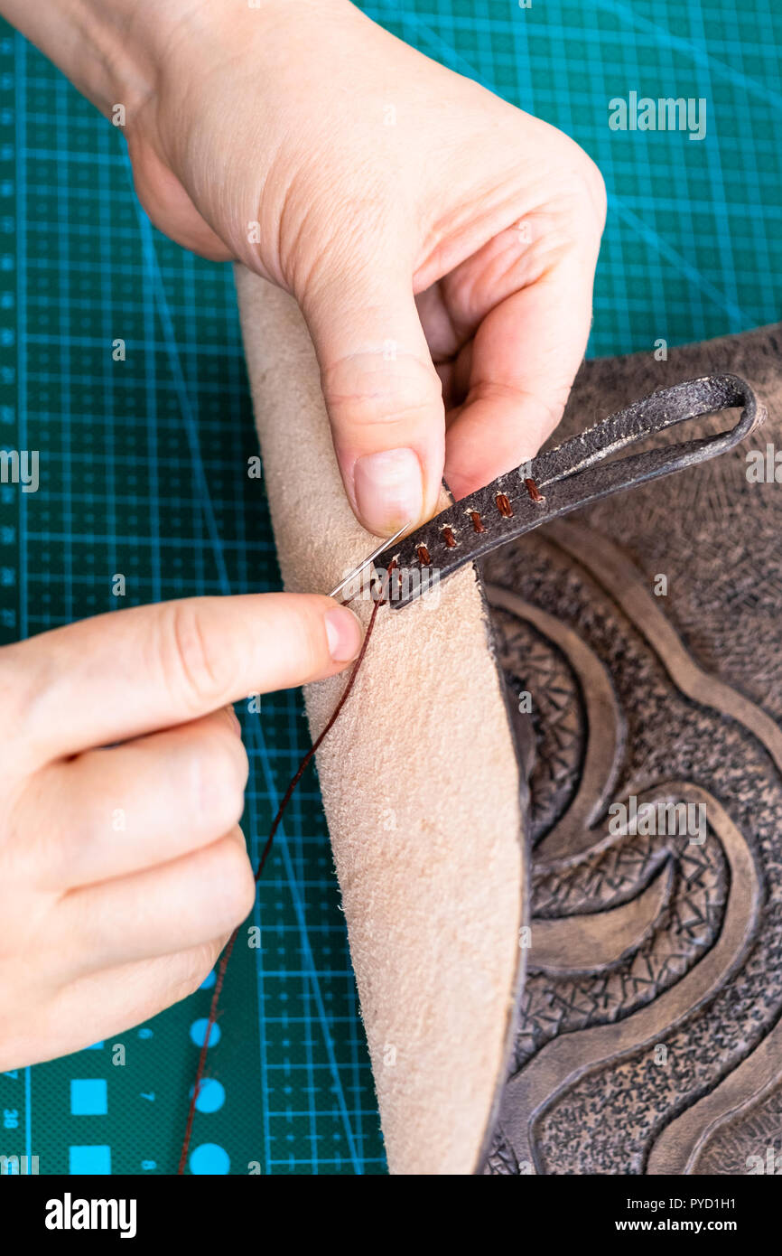workshop of making the carved leather bag - craftsman sews a loop for fastening handbag - Stock Image