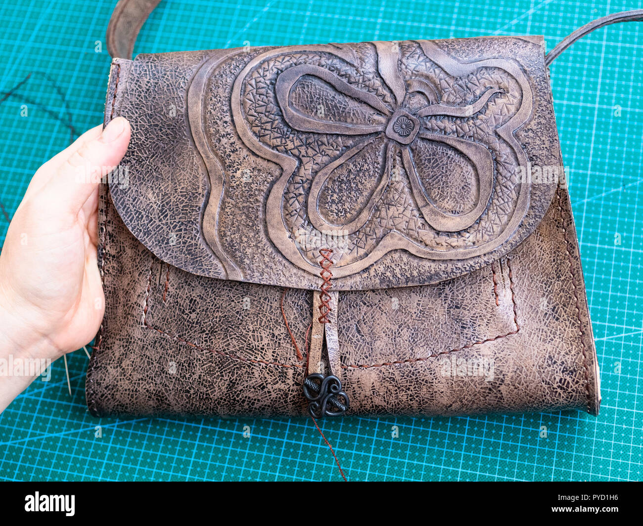 workshop of making the carved leather bag - craftsman shows the carved flap of the handbag - Stock Image