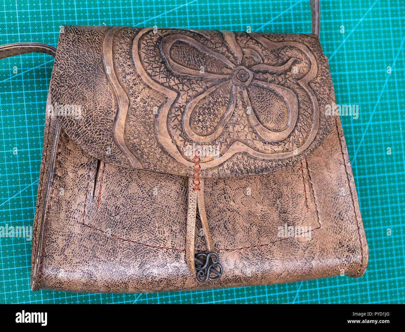 workshop of making the carved leather bag - view of the wet handbag polished by wax - Stock Image