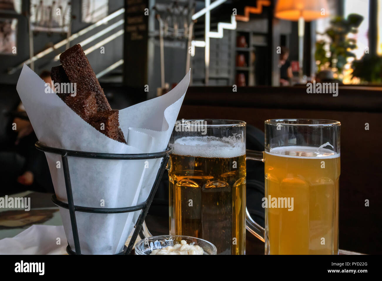 Two glasses of fresh beer different varieties and salty snack, real scene in pub, bar. Oktoberfest, beer festival concept - Stock Image