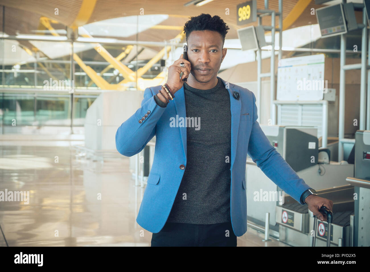 One young and attractive black businessman is walking in the airport terminal near the check-in desks while talking by mobile telephone. - Stock Image