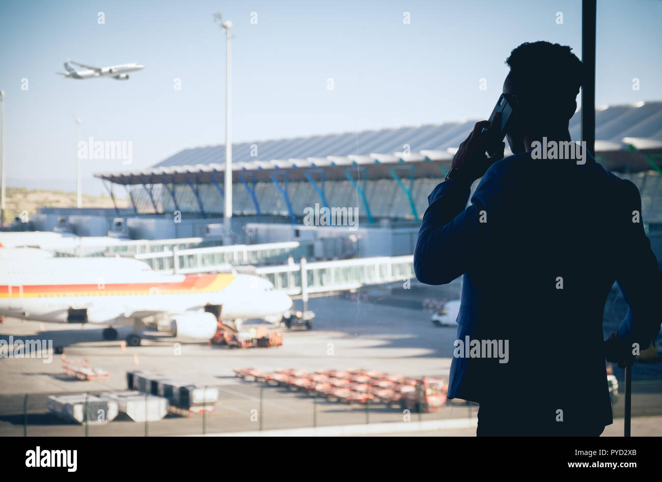 One young and attractive businessman is looking through the window in the airport terminal. An aeroplane is flying while others are parked on the land - Stock Image