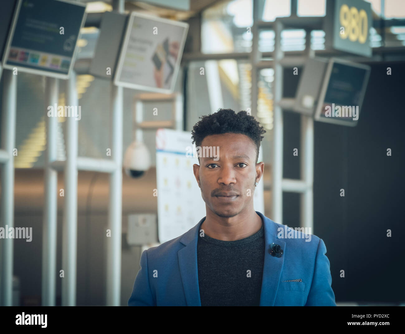 Closeup of one young and attractive black businessman waiting in the airport terminal near the check-in desks looking at the camera. He is wearing for - Stock Image