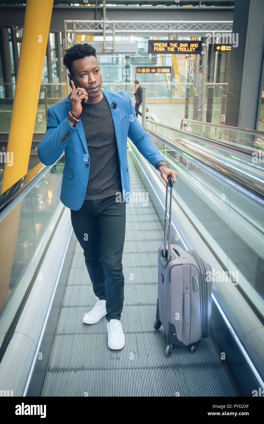 One young and attractive black businessman is walking on a mechanic ramp in the airport terminal while talking by mobile telephone. He is carrying a s - Stock Image
