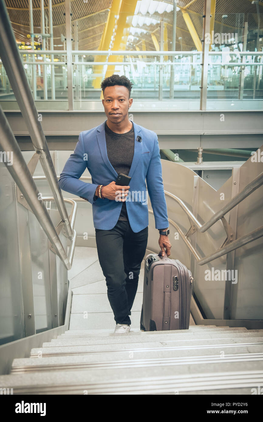 One young and attractive black businessman is climbing stairs in the airport terminal while talking by mobile telephone. He is carrying a suitcase and - Stock Image