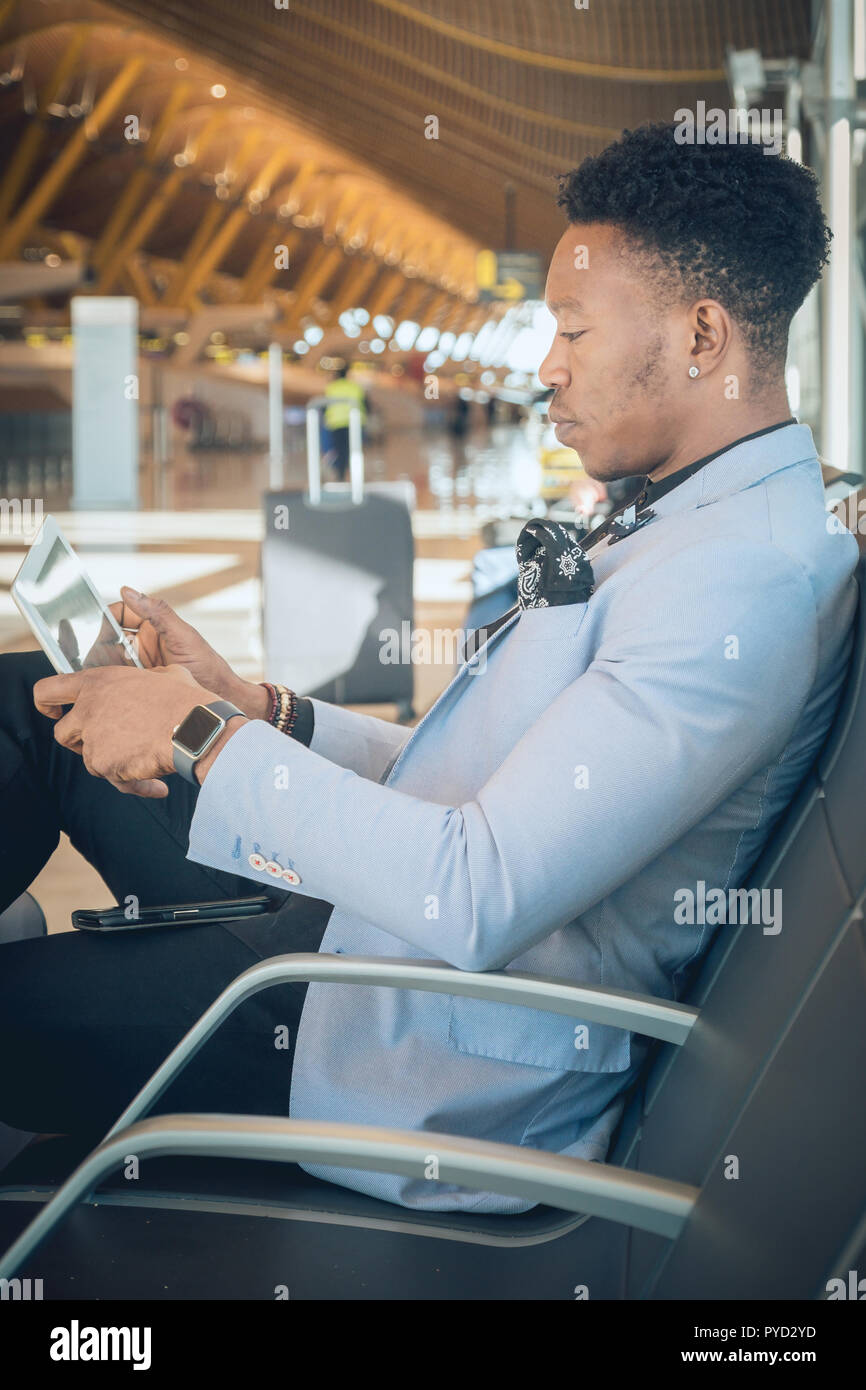 One young and attractive black businessman is seated in the airport terminal near the check-in desks while checking his tablet. He is carrying a suitc - Stock Image