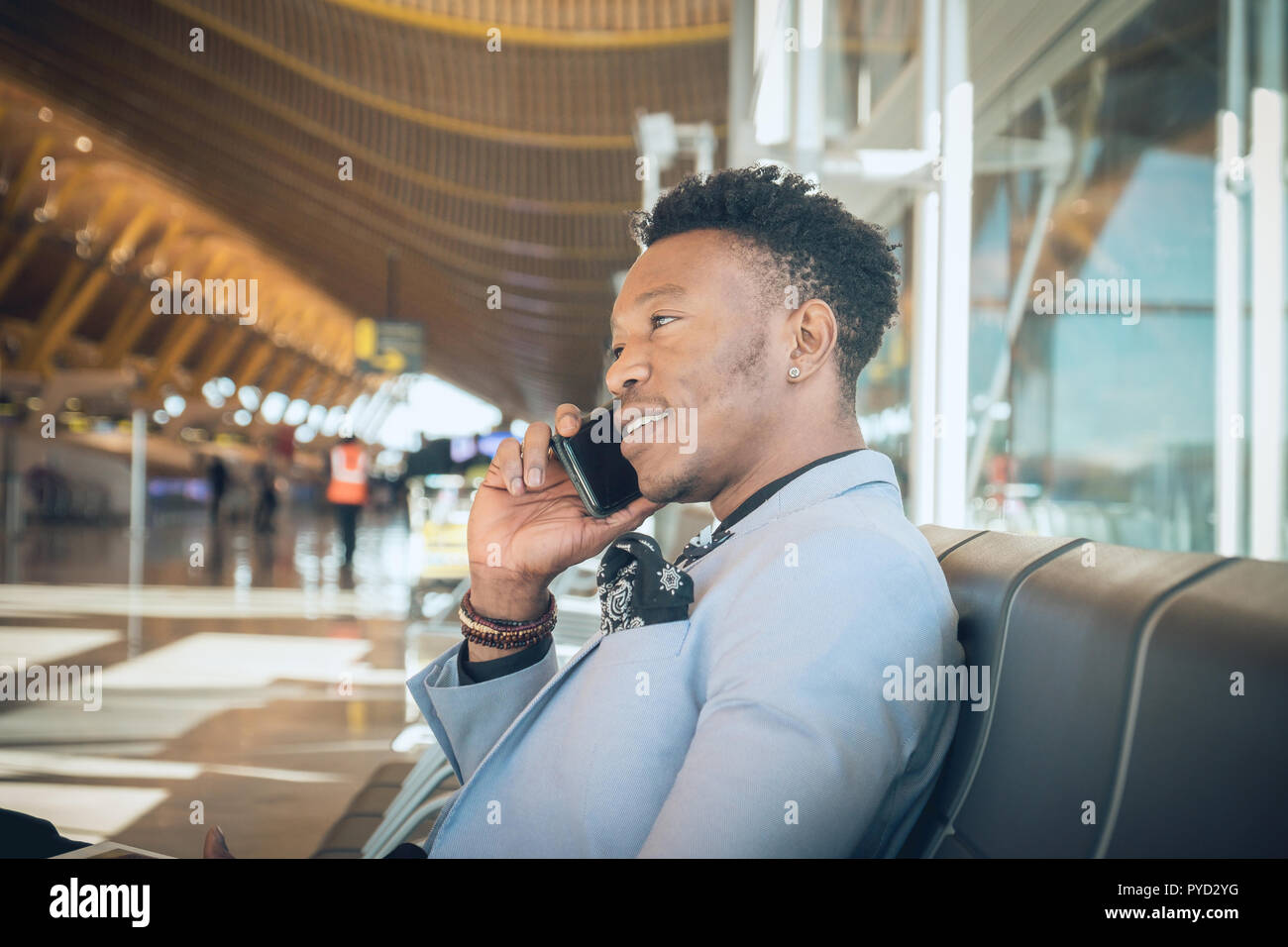 One young and attractive black businessman is seated in the airport terminal near the check-in desks, smiling and talking by telephone. He is carrying - Stock Image